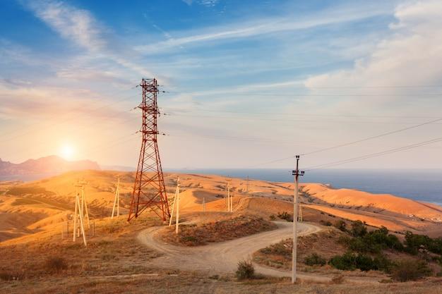Torre de alta tensão nas montanhas ao pôr do sol