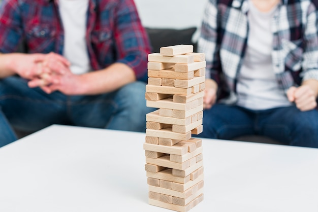 Torre de bloco de madeira na mesa branca na frente do casal sentado no sofá