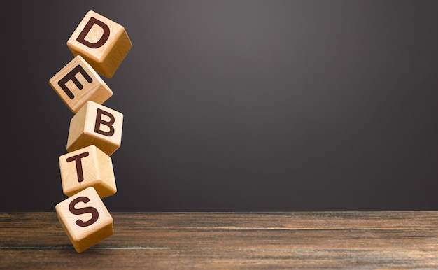 Torre de blocos em colapso instável e a palavra dívidas.