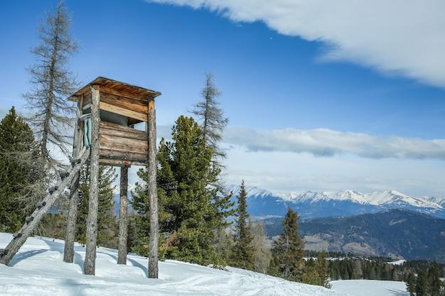 Torre de caça de madeira na floresta de inverno nas montanhas