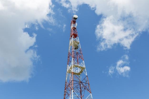 Torre de celular no fundo do céu azul nublado. vista de baixo
