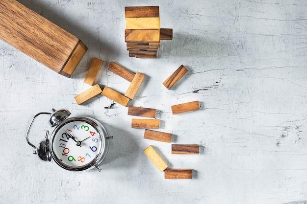 Torre de construção jenga e relógio na madeira tebla