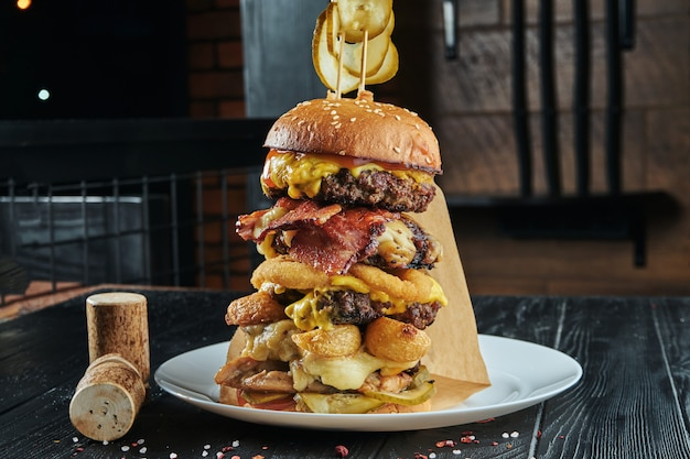 Torre de hambúrguer enorme com 5 costeletas de carne, queijo derretido, cebola, batata, pepino, molho. feche acima, vertical
