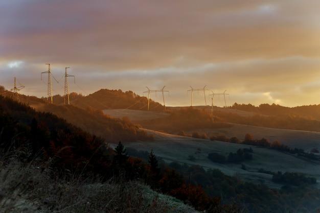 Torre de linhas de energia na névoa antes do amanhecer na periferia