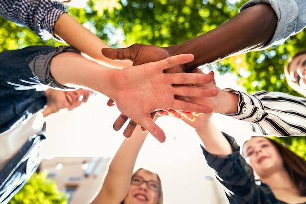 Torre de mãos de amigos caucasianos e afro-americanos juntos ao ar livre no dia quente e ensolarado de primavera