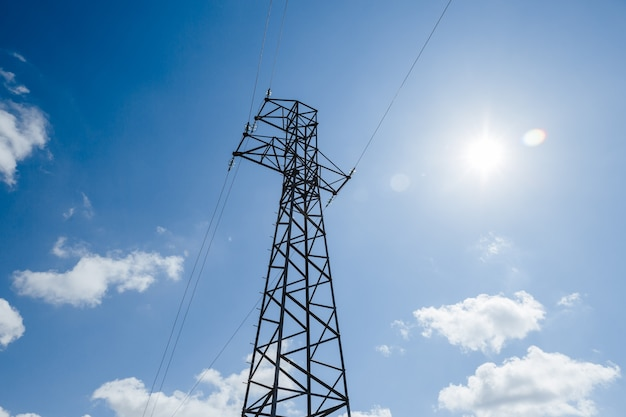 Torre de metal de alta tensão em um fundo de céu azul com fonte de alimentação de nuvens brancas