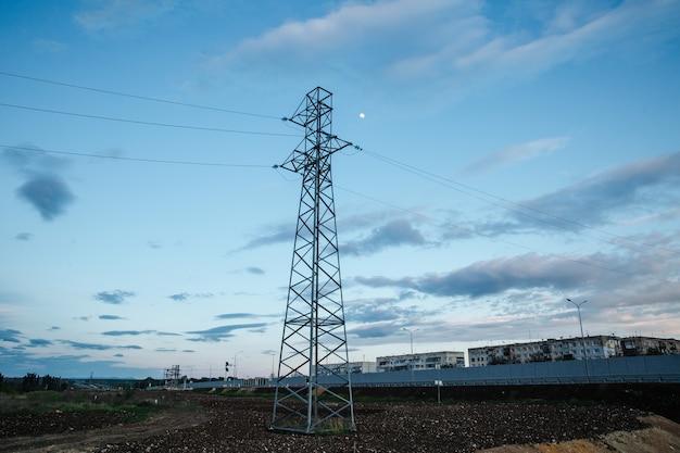 Torre de metal de alta tensão em um fundo do sol