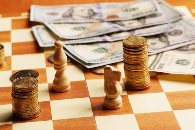 Torre de moedas e dólares em um tabuleiro de xadrez, dinheiro, conceito de finanças