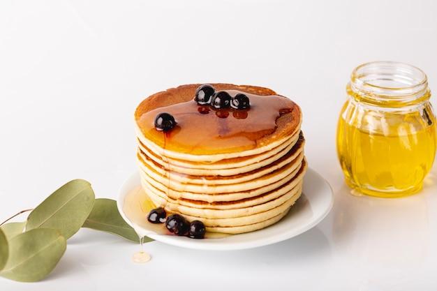 Torre de panqueca no prato com mirtilos e pote de mel