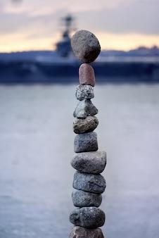 Torre de pedras com um navio como pano de fundo