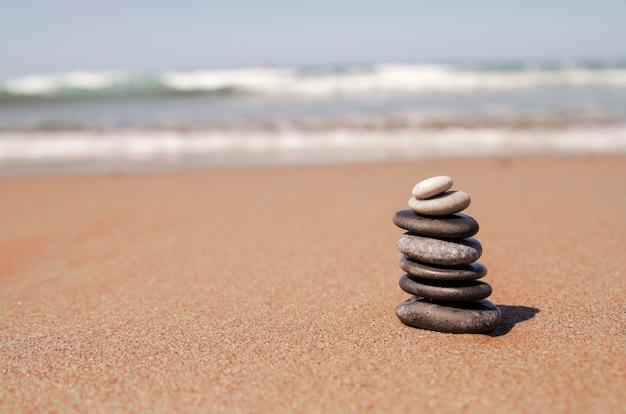 Torre de pedras de seixo na praia de areia. conceito de zen saldo