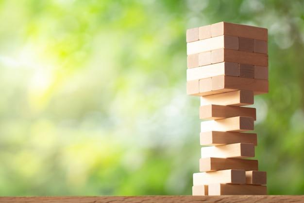 Torre de pilha de madeira de brinquedo de blocos de madeira na vegetação turva fundo