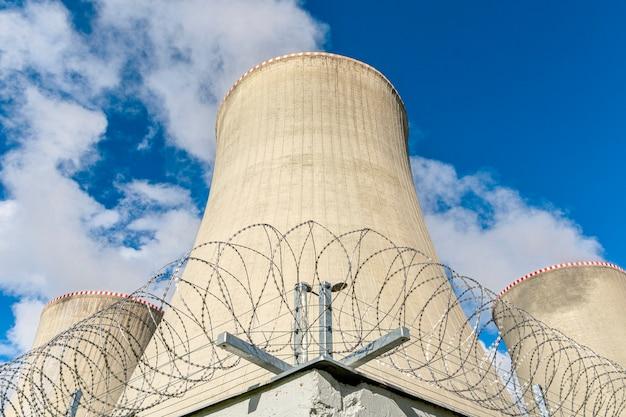 Torre de resfriamento de uma usina nuclear atrás de um objeto de arame farpado sob proteção estrita