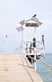Torre de resgate na costa do pontão. um corvo sentado em um gazebo branco à beira-mar