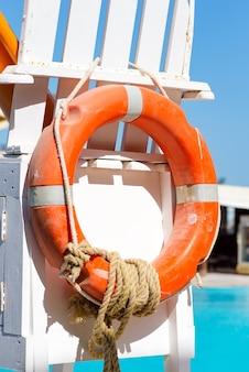 Torre de salva-vidas de praia de madeira com equipamento salva-vidas - salva-vidas, corda e outras coisas perto de tanque de natação