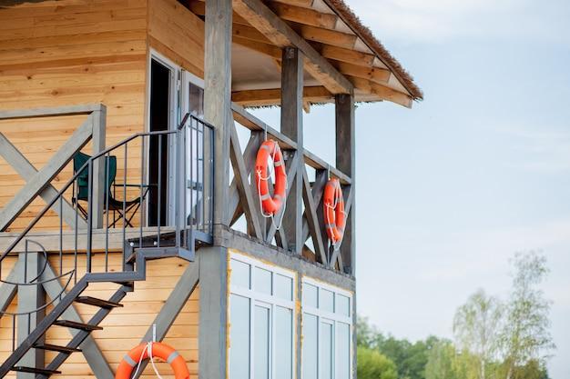 Torre de salva-vidas para resgate baywatch na praia. casa de madeira na beira-mar no fundo do céu nublado. férias de verão e resort. proteção pública e conceito de segurança