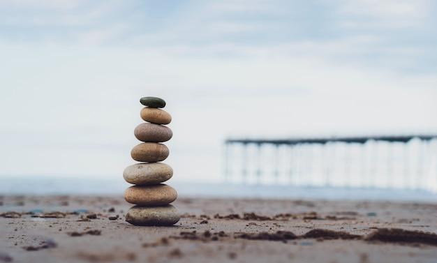 Torre de seixos à beira-mar com cais desfocado até ao mar