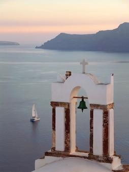Torre de sino da igreja ortodoxa grega contra o mar egeu com barco à vela no pôr do sol, santorini, grécia