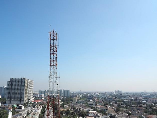 Torre de telecomunicações de cor vermelha e branca e céu azul.