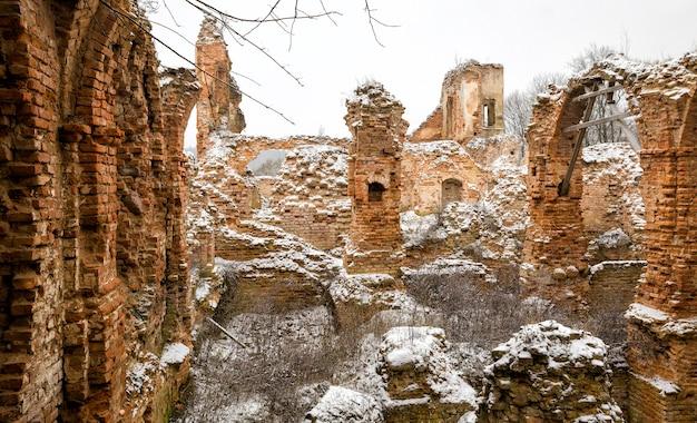 Torre de tijolos antigos em ruínas e paredes de fortaleza, arcos antigos feitos de tijolo vermelho
