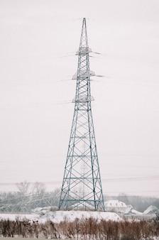 Torre de transmissão de energia no campo nevado.
