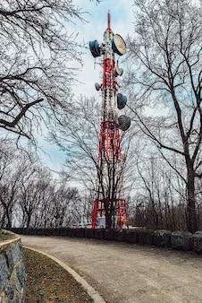 Torre de tv ao lado da estrada de asfalto, céu dramático, estrada rural velha da montanha da floresta com cerca de pedra.