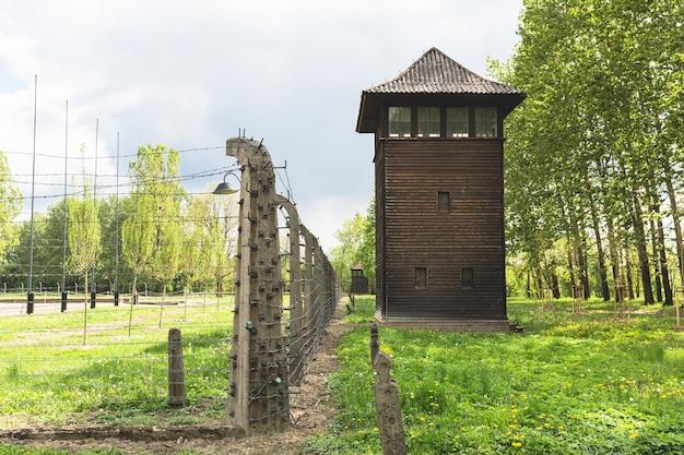 Torre de vigia e cerca de arame farpado no território do campo de concentração alemão auschwitz ii, polônia.