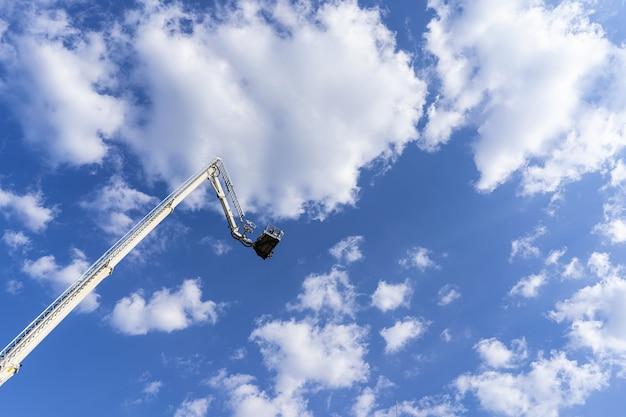 Torre do carro para elevar pessoas a uma grande altura no fundo do céu azul.