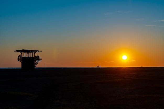 Torre do salva-vidas ao pôr do sol na praia de poti, na geórgia. vista incrível do pôr do sol.