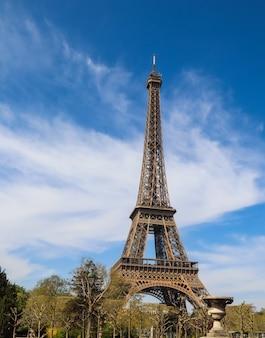 Torre eiffel em paris, frança contra céu azul com nuvens abril