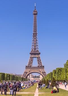 Torre eiffel em um dia ensolarado e claro um campo de marte repleto de pessoas em primeiro plano paris frança