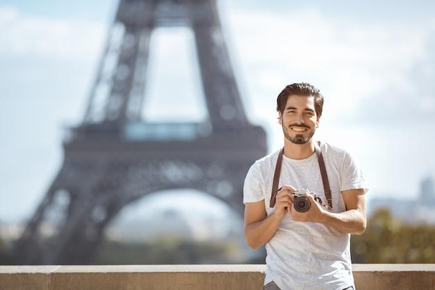 Torre eiffel turista com câmera tirando fotos em frente à torre eiffel, paris,