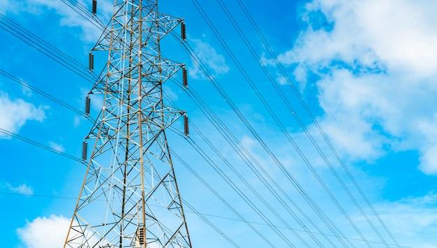 Torre elétrica de alta tensão e linhas de transmissão. postes de eletricidade com céu azul e nuvens brancas. conservação de energia e energia. torre de grade de alta tensão com cabo de aço.