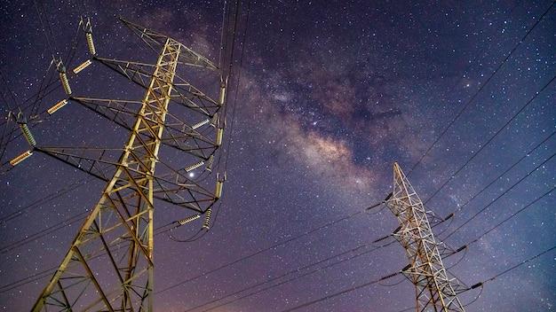 Torre elétrica de alta tensão no fundo do céu da via láctea.