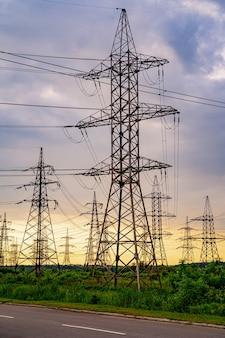 Torre elétrica de alta tensão. silhueta na hora do sol. postes de energia no fundo do tempo do sol. foco seletivo