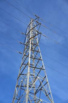 Torre elétrica vista de baixo do céu azul
