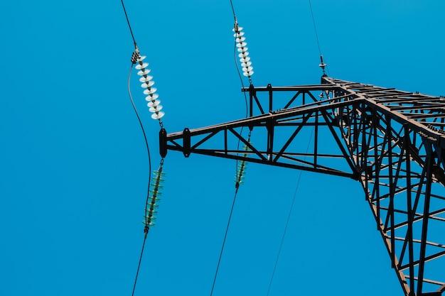 Torre enferrujada de alta tensão contra o céu azul