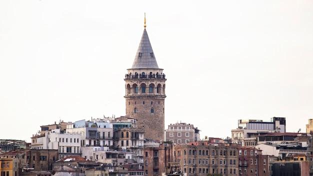Torre galata com níveis de edifícios residenciais em frente a tempo nublado em istambul, turquia