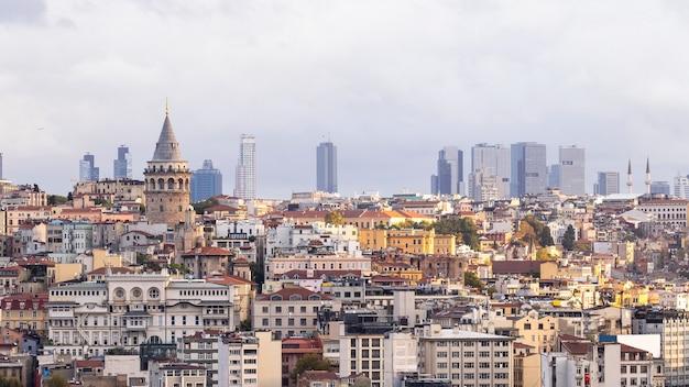 Torre galata com níveis de edifícios residenciais em frente e edifícios modernos com tempo nublado em istambul, turquia