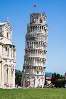 Torre inclinada com um edifício religioso ao lado Foto Premium