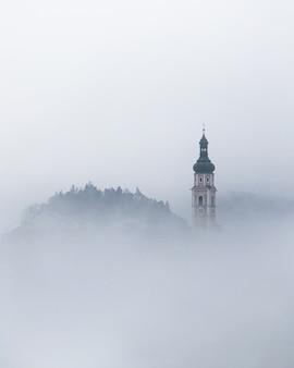 Torre no meio do nevoeiro na aldeia de castelrotto nas dolomitas italianas