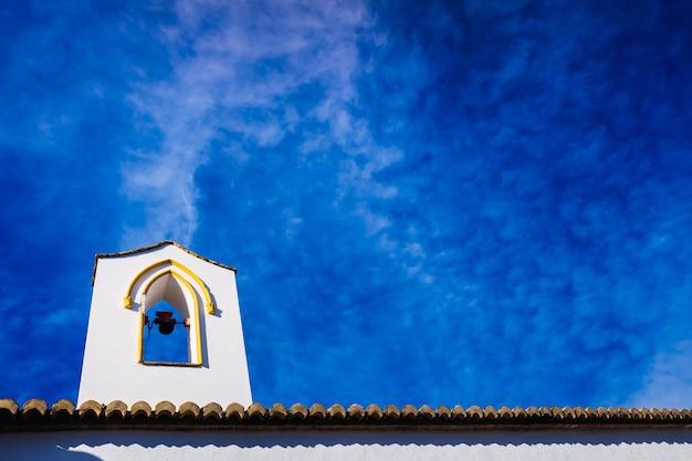 Torre sineira de uma igreja com paredes brancas, no contexto de um lindo céu azul.