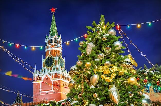 Torre spasskaya na praça vermelha em moscou e árvore de ano novo com brinquedos em uma noite de inverno