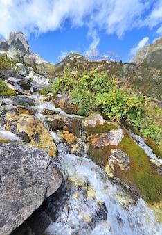 Torrente alpina fluindo nas rochas com uma cordilheira de fundo