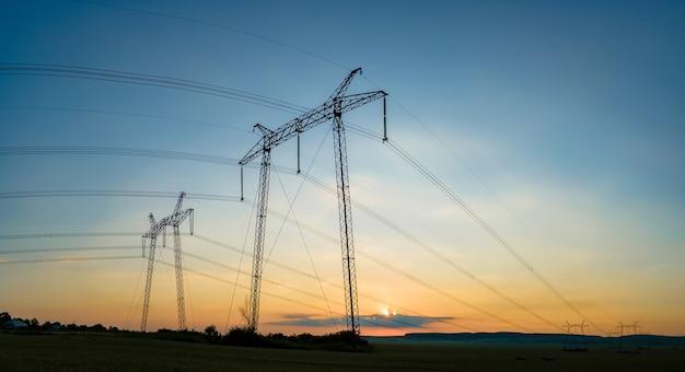 Torres de alta tensão com linhas de energia elétrica ao pôr do sol.