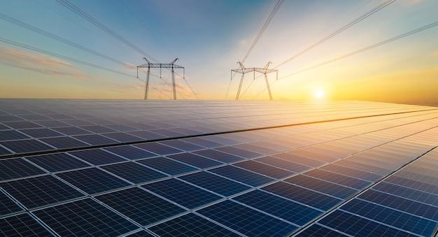 Torres de alta tensão com linhas de energia elétrica, transferindo energia de painéis solares fotovoltaicos ao pôr do sol. produção do conceito de eletricidade sustentável.