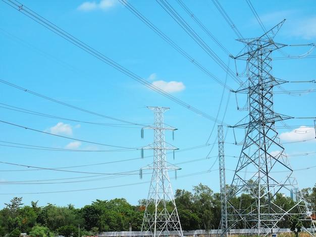 Torres de alta tensão e linhas de energia contra o céu nublado azul vibrante