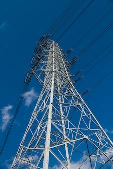 Torres de alta tensão têm o céu para trás.