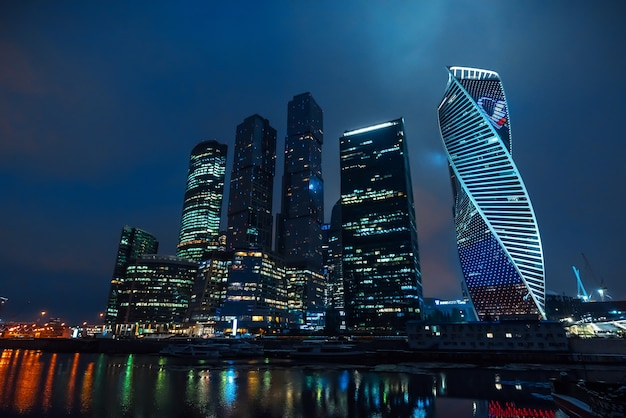 Torres de arranha-céus da cidade de moscou à beira do rio com reflexo à noite