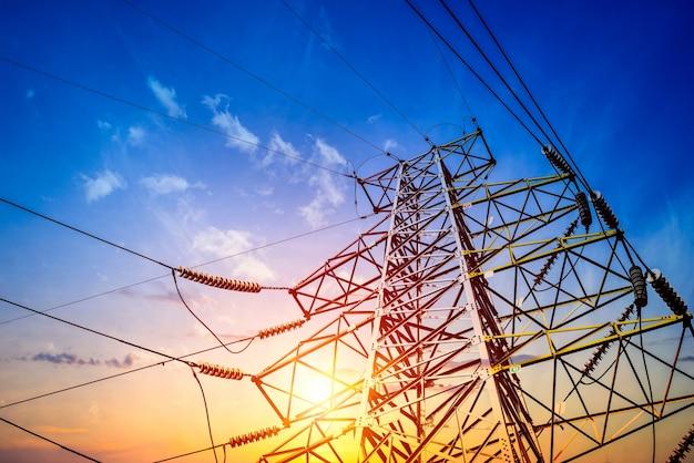 Torres de eletricidade no laranja do sol
